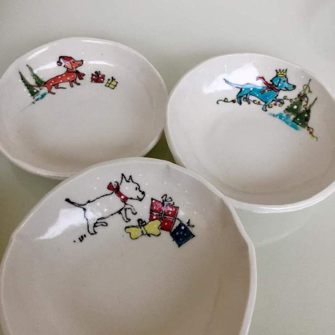 Hand-made porcelain dishes with hand-drawn little dogs in the snow by Mary Funk-Butterworth. For sale at the Putney School of Art and Design Christmas Fair